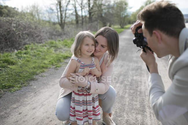 Joven tomando fotos de su familia con cámara - foto de stock