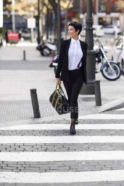 Smiling young businesswoman crossing street — Stock Photo