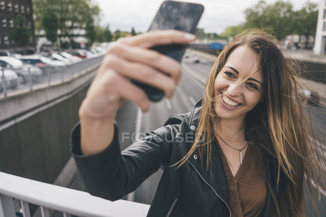 Smiling young woman taking a selfie on motorway bridge — Stock Photo