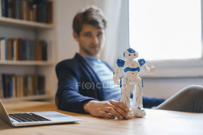 Homme assis à table avec un robot — Photo de stock