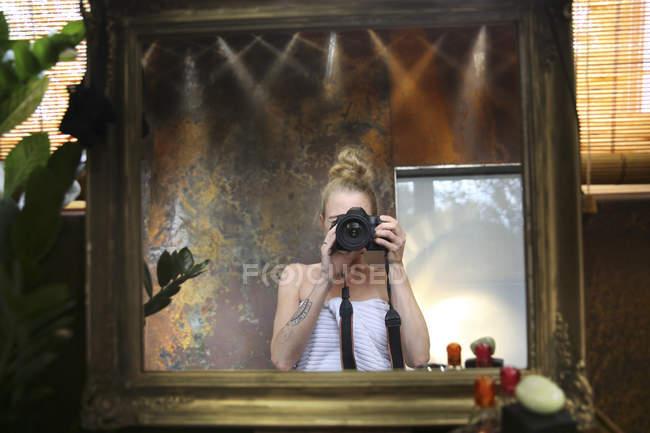 Imagem espelhada de mulher tomando selfie com câmera no banheiro — Fotografia de Stock