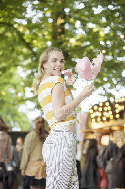 Portrait of young woman with pink candy floss on streetfood festival — Stock Photo