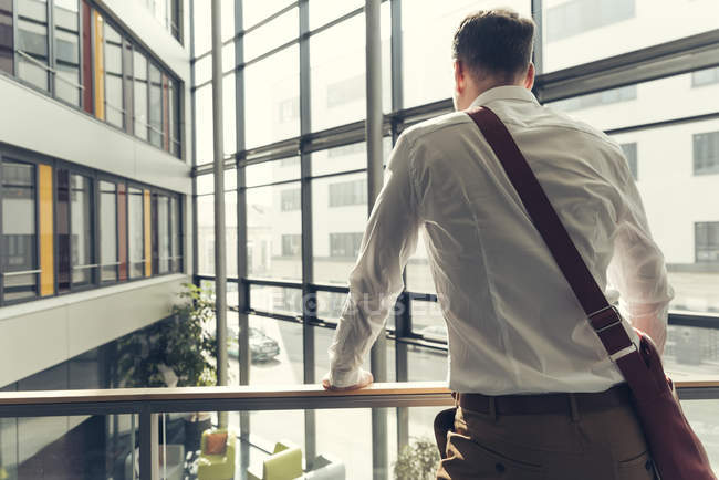 Rear view of businessman standing in office building leaning on railing — Stock Photo