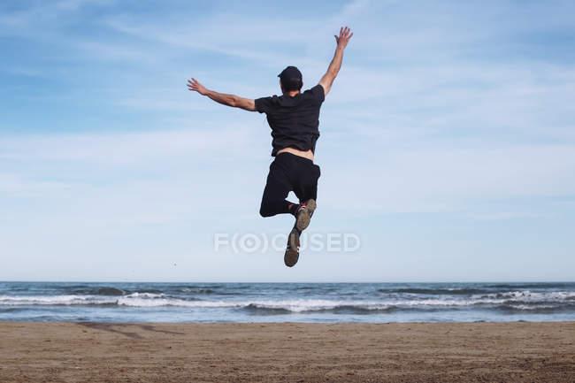 Vue arrière de l'homme sautant dans les airs sur la plage — Photo de stock
