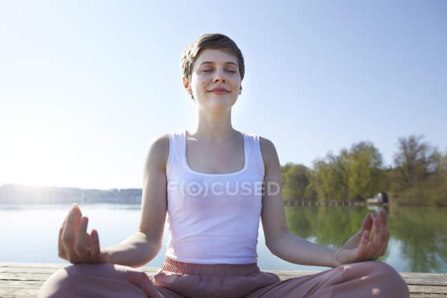 Портрет женщины, практикующей йогу на пристани у озера — стоковое фото