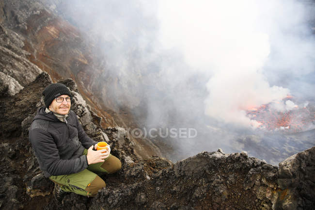 Africa, Democratic Republic of Congo, Virunga National Park, Man sittiing over Nyiragongo volcano crater — Stock Photo