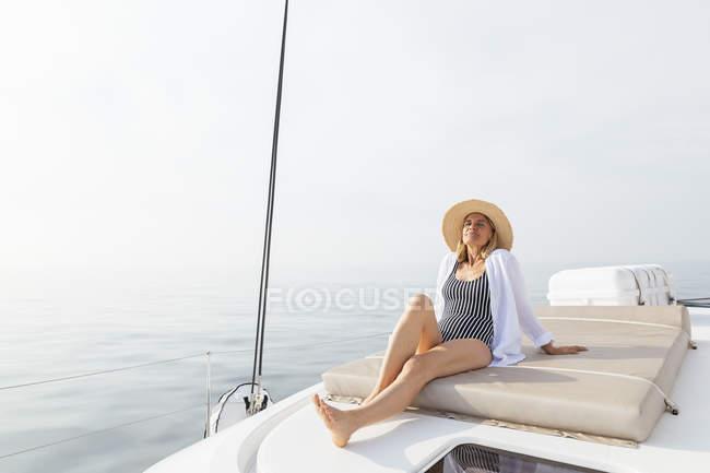Mature woman relaxing on a catamaran, taking a sunbath — Stock Photo