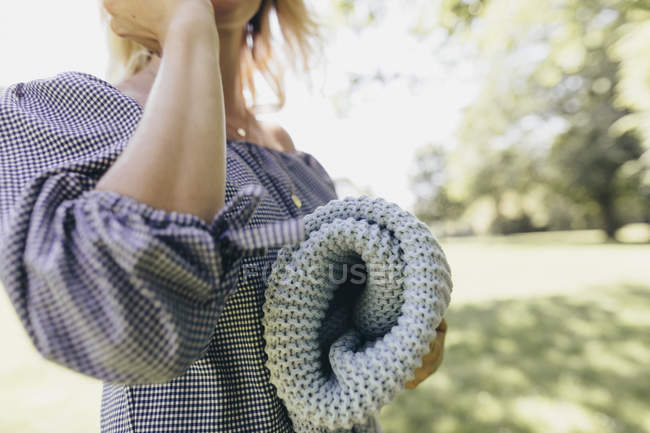 Young woman holding blanket in a park — Stock Photo