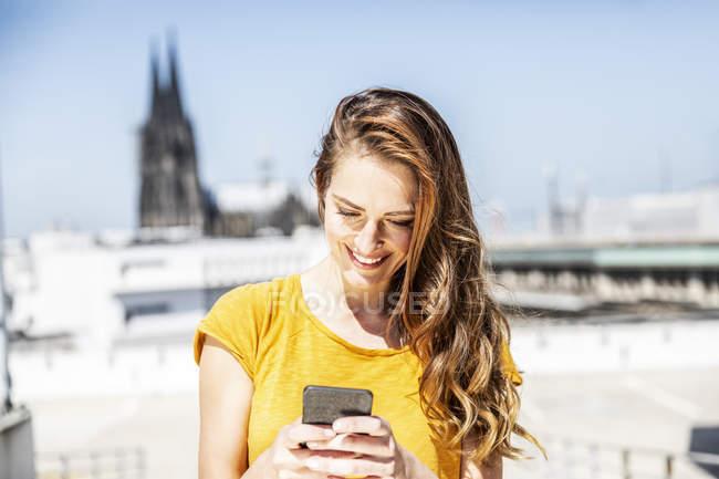 Германия, Кельн, улыбающаяся женщина с мобильного телефона — стоковое фото