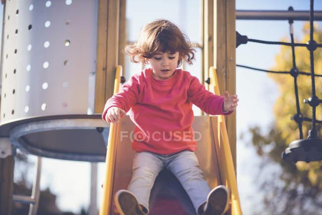 Retrato de menina sentada em slide no parque infantil — Fotografia de Stock