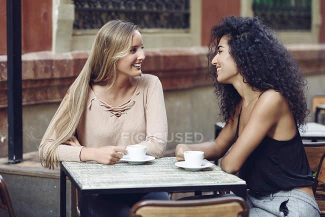 Dois amigos bebendo café no café da calçada — Fotografia de Stock