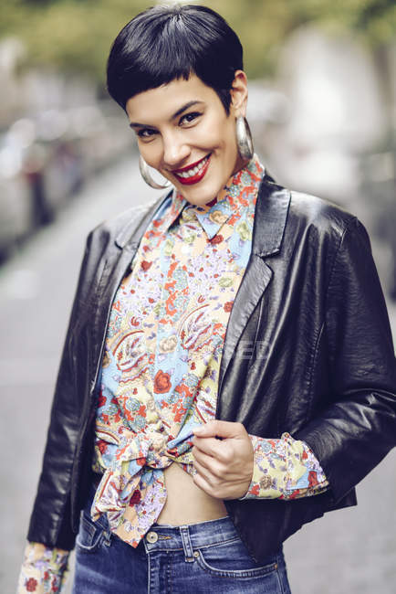 Portrait of fashionable young woman wearing patterned blouse and leather jacket — Stock Photo