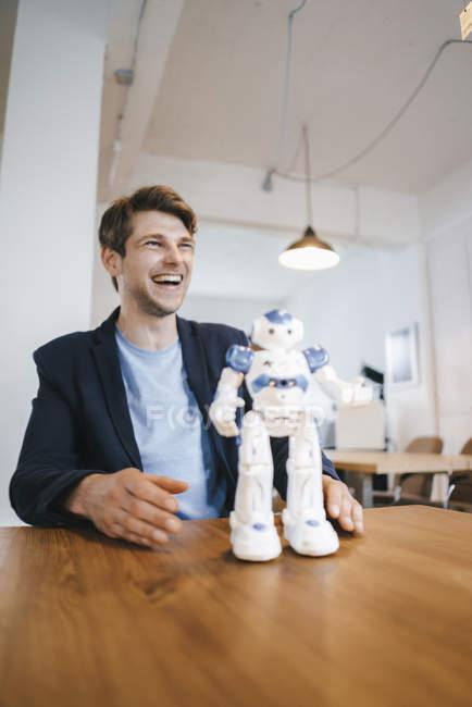 Un homme riant avec un robot sur la table — Photo de stock