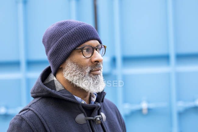 Portrait of african american man wearing blue woolly hat watching something — Stock Photo