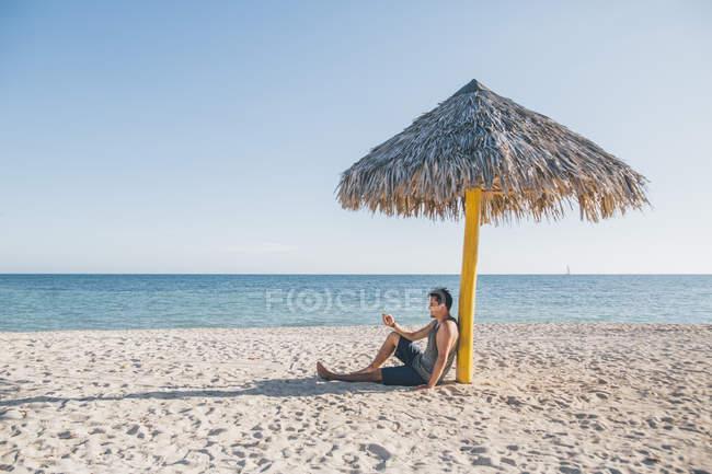 Куба, молодий чоловік, сидячи під парасолькою в Плайя-Анон — стокове фото