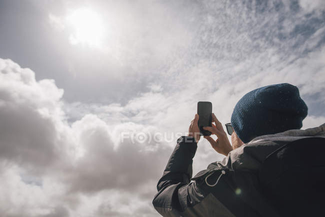 Man holding up cell phone under sunny sky with clouds — Stock Photo