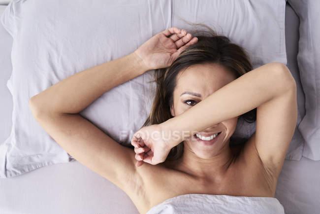 Ritratto di donna sorridente sdraiata a letto che nasconde il viso — Foto stock