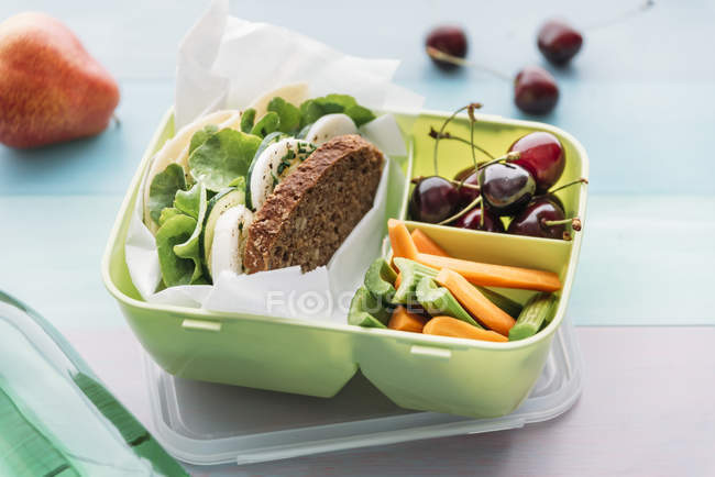 Healthy school food in a lunch box, vegetarian sandwich with cheese, lettuce, cucumber, egg and cress, sliced carrot and celery, cherries and pear — Stock Photo
