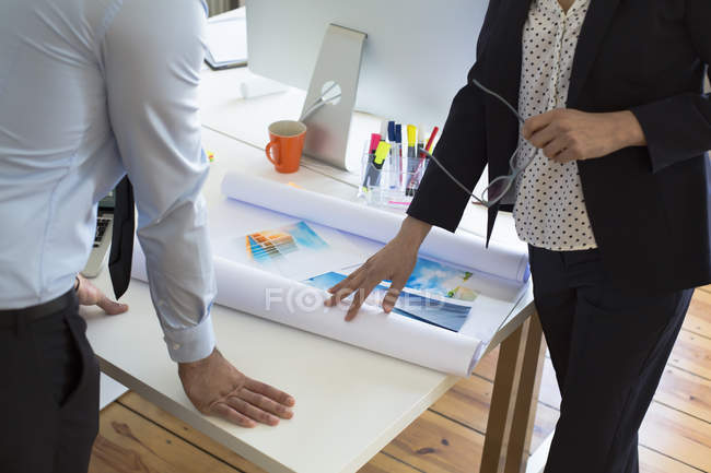Businessman and businesswoman with printouts in office — Stock Photo