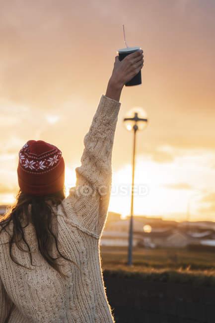 Islanda, giovane donna con caffè per andare al tramonto — Foto stock
