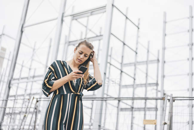 Young woman using cell phone at scaffolding — Stock Photo