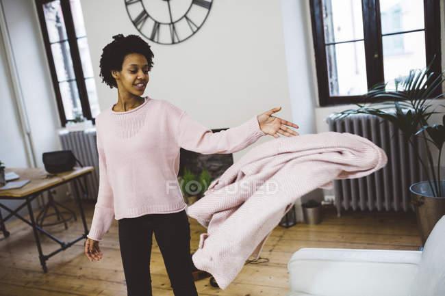 Africana americana mujer llegar a casa, lanzando abrigo en sofá - foto de stock
