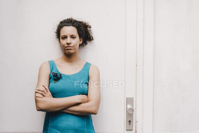 Mulher cruzando braços, de pé na frente da porta — Fotografia de Stock