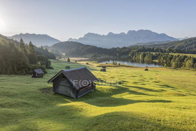 Alemanha, Baviera, Werdenfelser Land, lago Geroldsee com celeiro de feno, no fundo as montanhas Karwendel — Fotografia de Stock