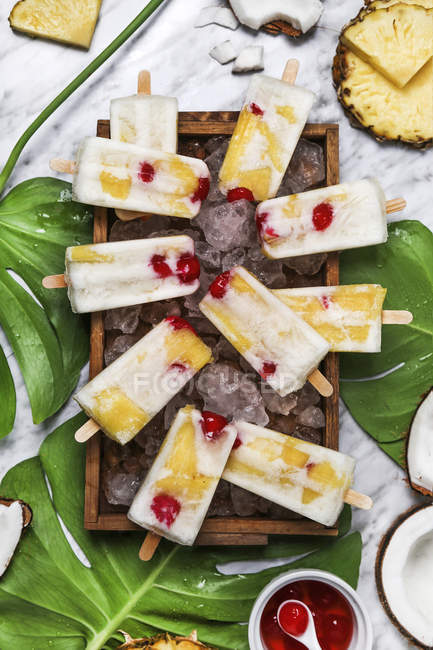 Pina Colada popsicles aux cerises confites et ananas sur feuilles — Photo de stock