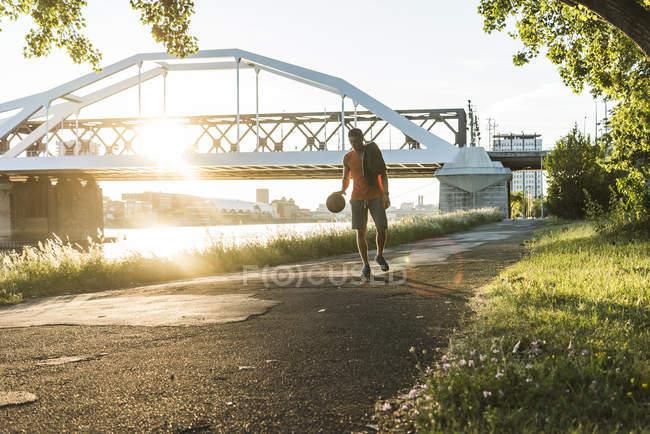 Young man dribbling basketball at the river — Stock Photo