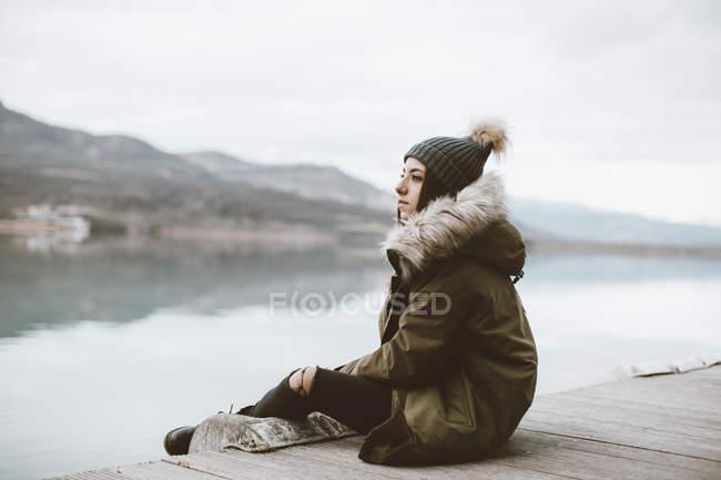 Pensativa joven sentada en embarcadero mirando a la distancia - foto de stock