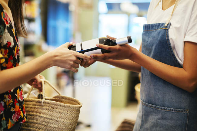 Shop assistant handing over wine bottle to customer in a store — Stock Photo