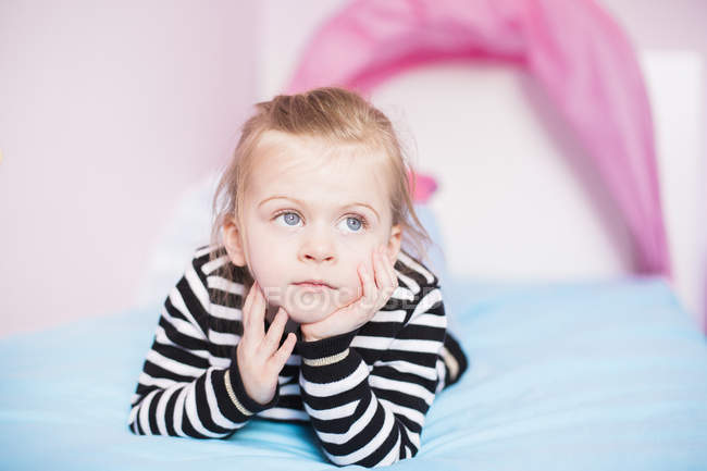 Portrait of daydreaming little girl lying on bed at home — Stock Photo