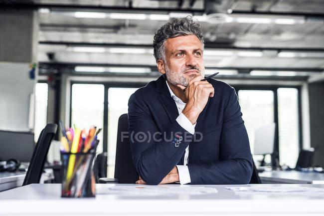 Confident mature businessman in office thinking — Stock Photo