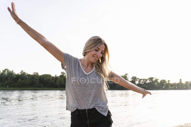 Mujer joven caminando a orillas del río, brazos levantados - foto de stock