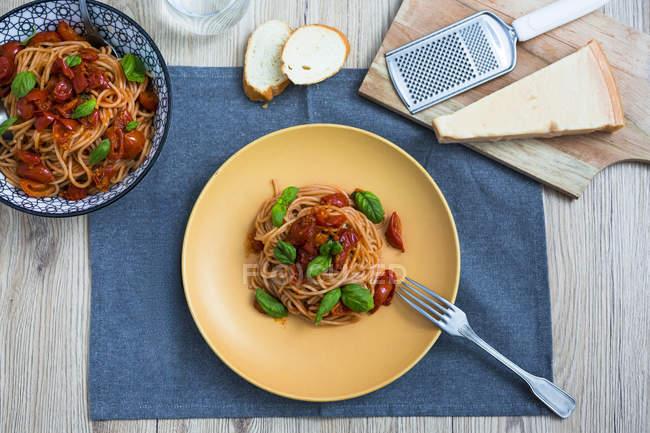 Vue du haut de Spaghetti avec des tomates cerises et basilic sur l'assiette — Photo de stock