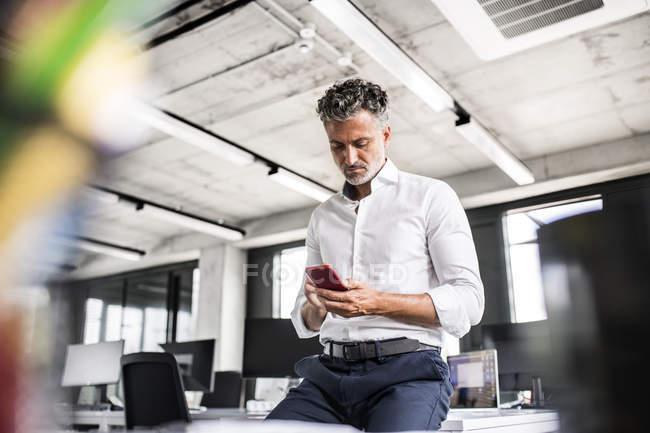 Mature businessman using cell phone in office — Stock Photo