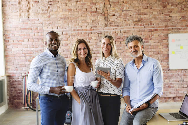 Portrait of smiling colleagues at desk in loft office — Stock Photo