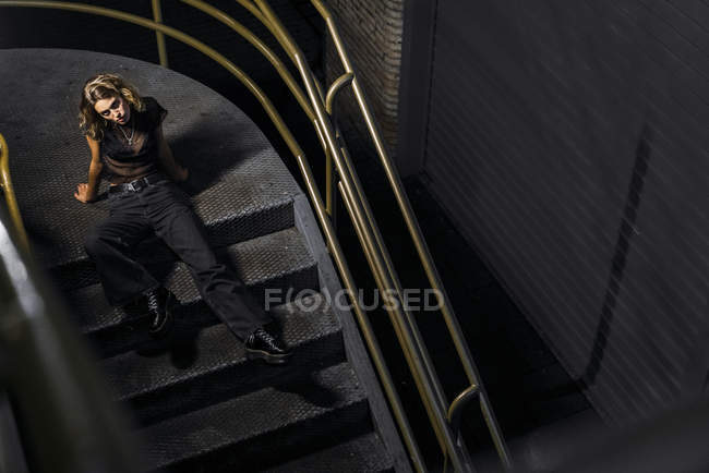 Élégante jeune femme assise dans les escaliers la nuit — Photo de stock