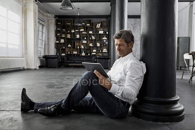 Homem maduro sentado no chão usando tablet digital em loft flat — Fotografia de Stock