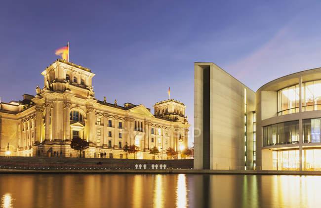 Deutschland, Berlin, Regierungsviertel, Reichstagsgebäude mit Deutschlandfahnen und Paul-Loebe-Gebäude an der Spree am Abend — Stockfoto