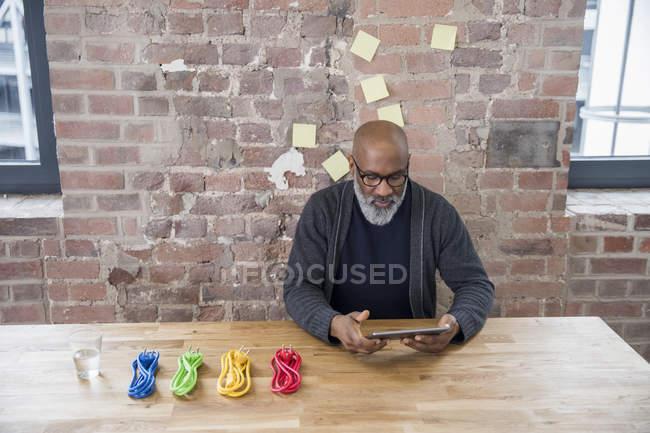 Homme d'affaires afro-américain avec tablette et câbles d'alimentation colorés à la table en bois — Photo de stock