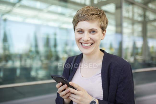 Retrato de una mujer de negocios rubia usando un smartphone - foto de stock