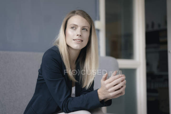 Portrait of pensive businesswoman with beverage — Stock Photo