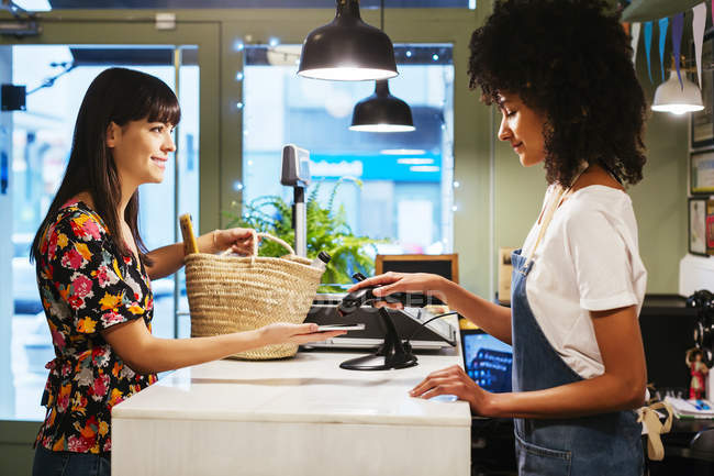 Customer paying cashless with smartphone at counter of a store — Stock Photo