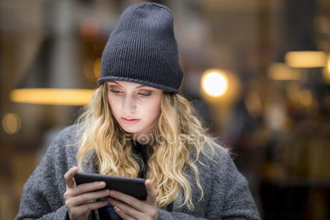 Портрет серьезной молодой женщины с помощью смартфона — стоковое фото