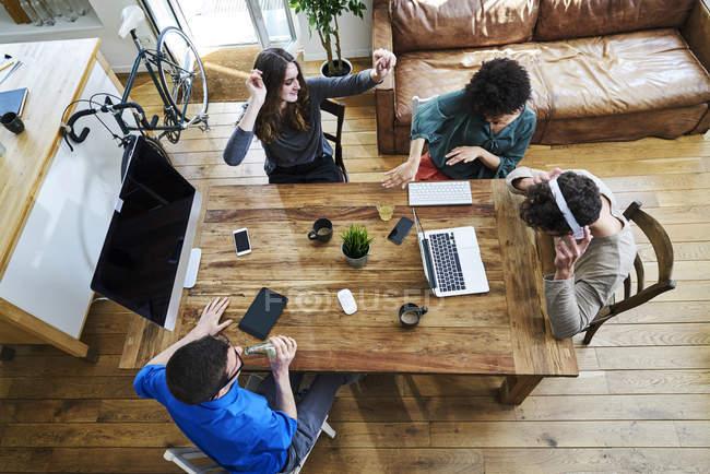 Vue surélevée de collègues écoutant de la musique à une table en bois au bureau — Photo de stock