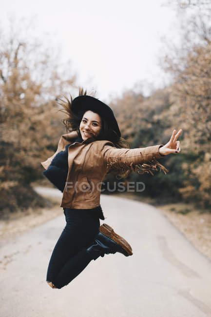 Ritratto di giovane donna felice che salta in aria all'aperto — Foto stock