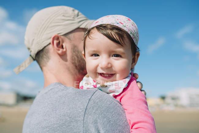 Retrato de la niña feliz en brazos de padre en la playa - foto de stock