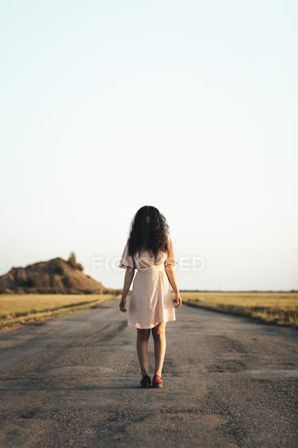 Молодая женщина, стоящая на проселочной дороге, прячет лицо за каштановыми волосами — стоковое фото